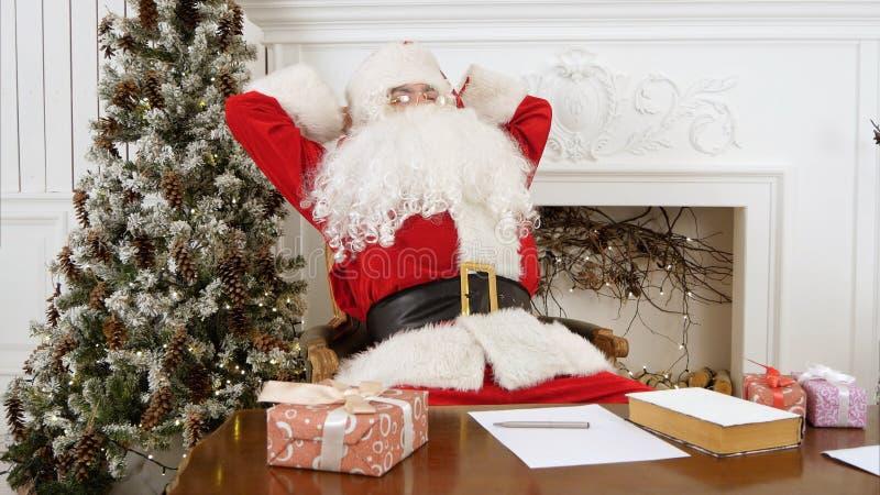 Müde Santa Claus, die von einem Haar aufwacht, um Geschenke, vorzubereiten fortzufahren lizenzfreies stockbild