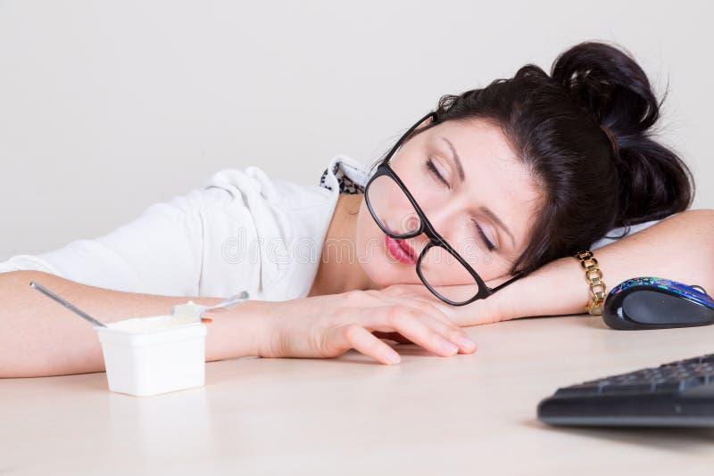 Müde schlafende Frau im Büro stockfotografie