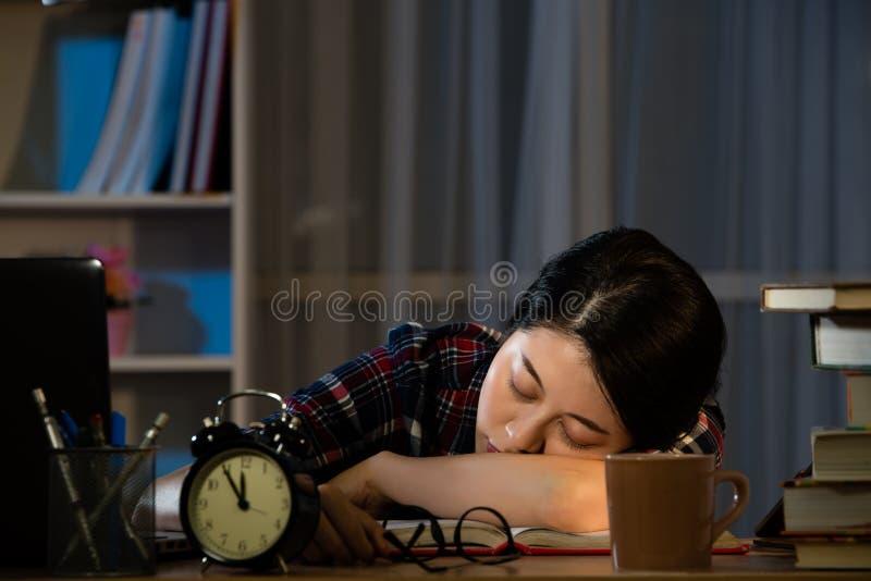 Müde Studenten, die das Schlafen auf dem Desktop studieren lizenzfreies stockbild