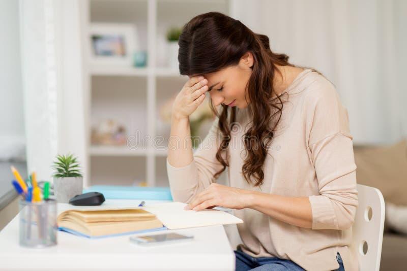 Müde Studentin mit dem Buchlernen zu Hause stockfoto