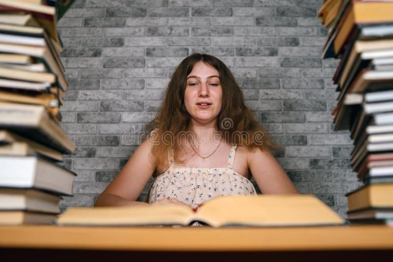 Müde Studentinlesung unter Büchern Nachdenkliche junge Frau, die bei Tisch mit Stapel des Buches sitzt und an liest stockfotografie