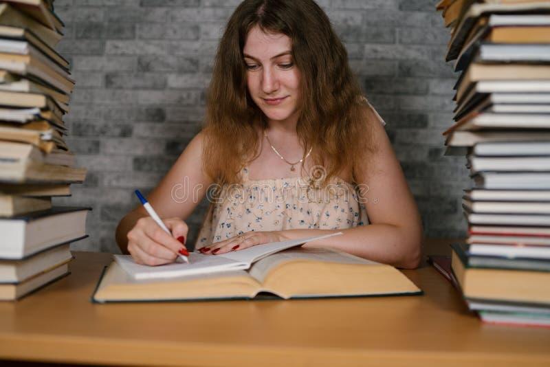 Müde Studentinlesung unter Büchern Nachdenkliche junge Frau, die bei Tisch mit Stapel des Buches sitzt und an liest stockfoto