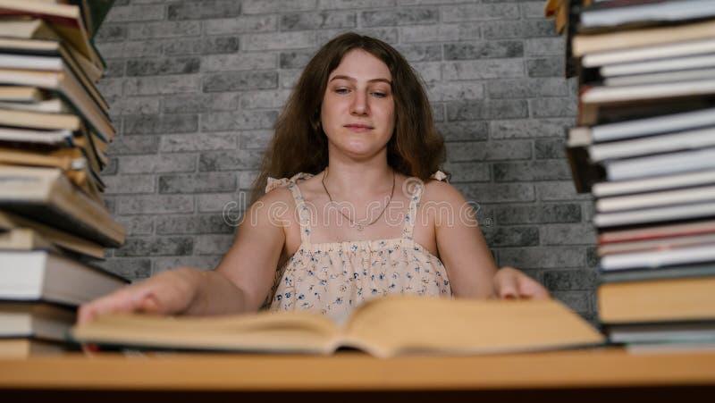Müde Studentinlesung unter Büchern Nachdenkliche junge Frau, die bei Tisch mit Stapel des Buches sitzt und an liest stockfotos