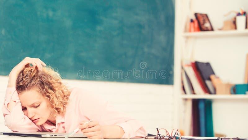 Müde Tutor schläft am Arbeitsplatz ein Müde Studierende lehnen sich auf dem Schreibtisch Abgasstunde Lehrer erschöpft nach harter lizenzfreies stockbild