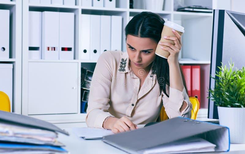 Müde und erschöpfte Frau betrachtet den Berg von Dokumenten Fristen für die Unterordnung von Berichten lizenzfreie stockfotografie
