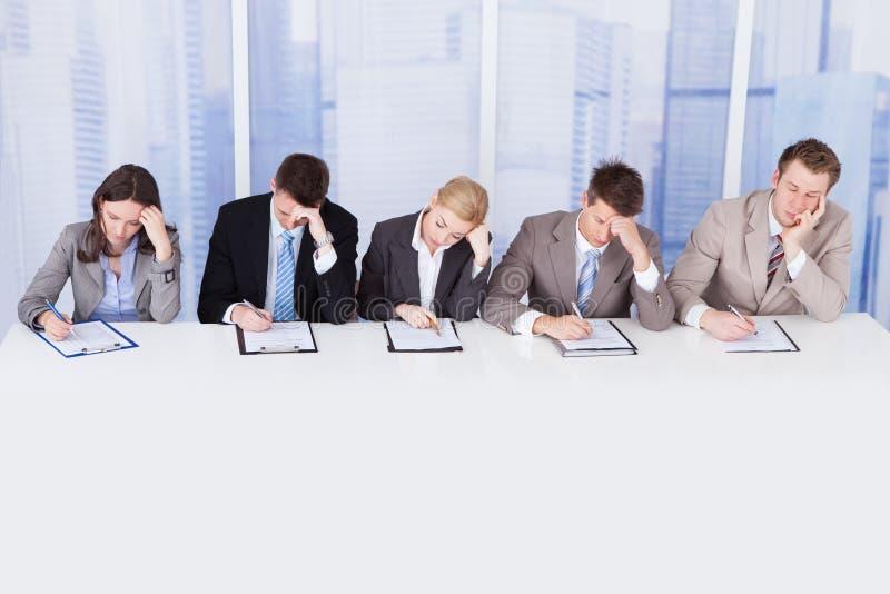 Müde Unternehmenspersonalreferenten bei Tisch stockfotos