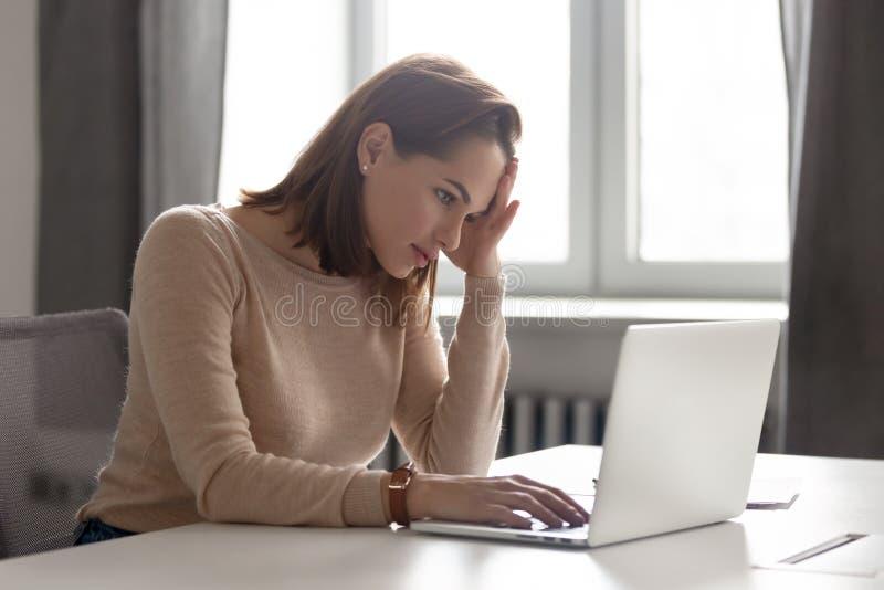 Müde weibliche Angestellte, die Kopf an Hand halten und Kopfschmerzen haben lizenzfreie stockfotos