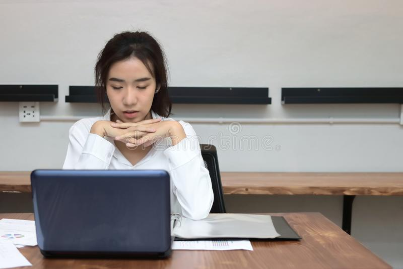 Müder überarbeiteter junger asiatischer Geschäftsfrauabschluß, den ihre Augen an Arbeitsplatz schlossen stockfotografie