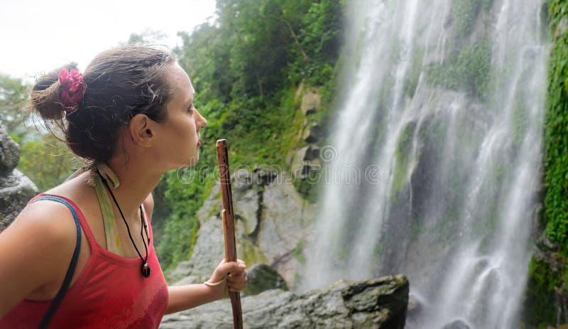 Müder, aber glücklicher Wanderer der jungen Frau, der einen Wasserfalldschungel betrachtet stockfoto