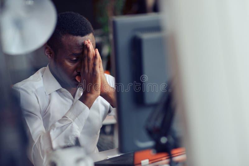 Müder afrikanischer Mann, der in einem Büro nach einem harten Arbeitstag, arbeitend auf dem Laptop sitzt und versuchen sich zu ko stockfotografie