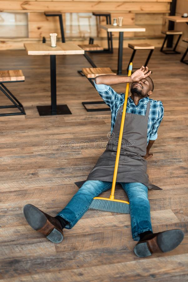 müder Afroamerikanermann, der auf Boden nachdem dem Kehren stillsteht lizenzfreies stockfoto