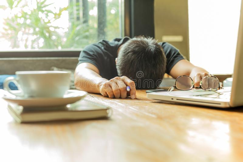 Müder asiatischer Mann mit Kopf unten auf Computerlaptop beim Arbeiten lizenzfreies stockbild