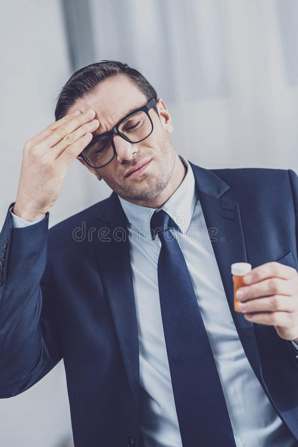 Müder Büroangestellter, der Kopfschmerzen hat stockfotografie