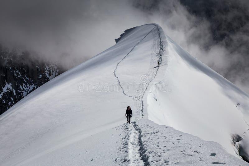 Müder Bergsteiger, der zurück zum Schutz auf der Spur läuft entlang die Kante des Berges geht  stockfotos