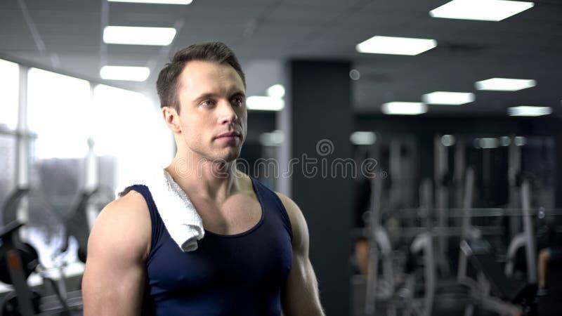 Müder Bodybuilder mit Tuch auf der Schulter, die nach hartem Training in der Turnhalle sich entspannt lizenzfreie stockfotos