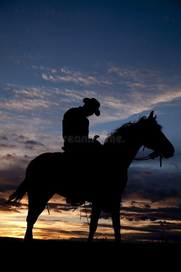 Müder Cowboy auf Pferd stockfotografie
