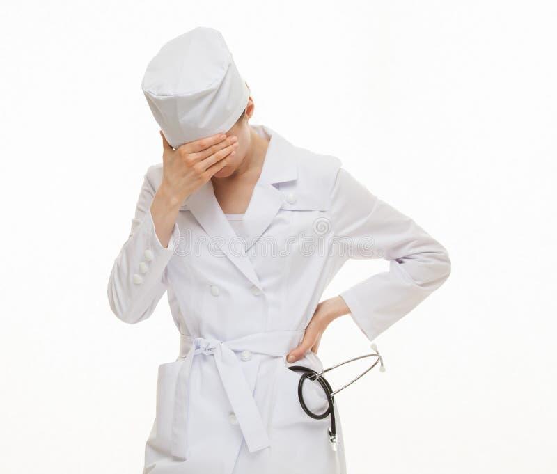 Müder Doktor, der ihr Gesicht schließt stockfotografie