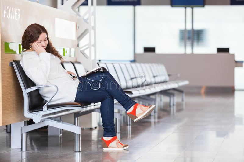 Müder Durchfahrtpassagier, der im Flughafen schläft stockbild