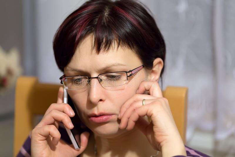Müder Frauenanruf telefonisch lizenzfreie stockfotografie