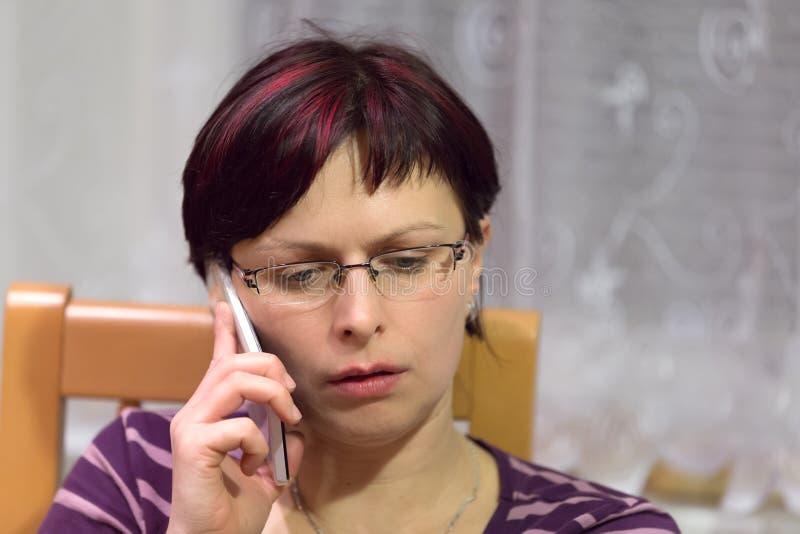 Müder Frauenanruf telefonisch lizenzfreies stockfoto