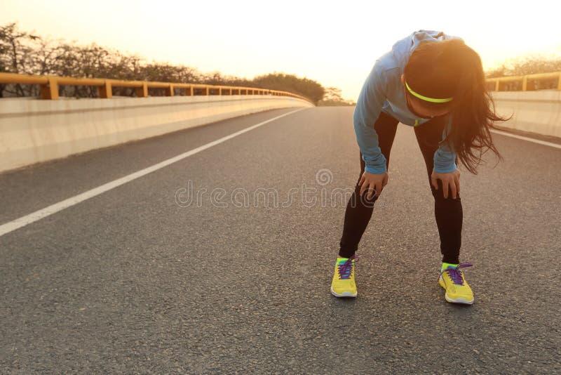 Müder Frauenläufer, der eine Pause macht stockfotografie