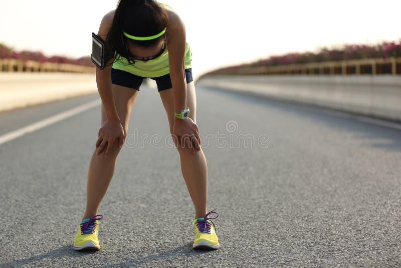 Müder Frauenläufer, der eine Pause macht, nachdem stark laufen stockfotografie