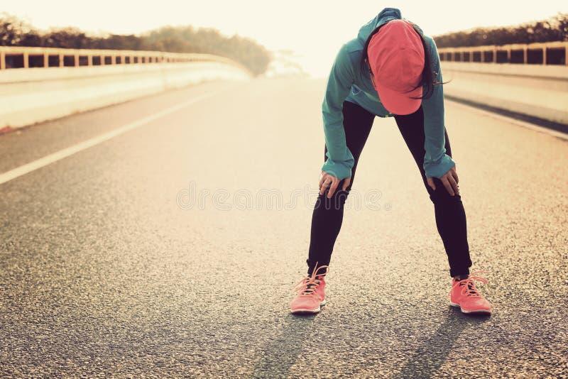 Müder Frauenläufer, der eine Pause macht, nachdem stark laufen stockfoto