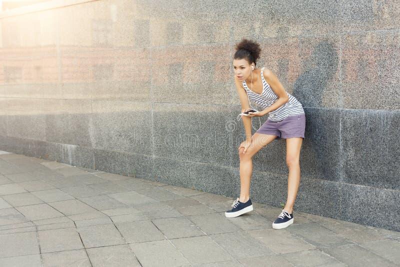 Müder Frauenläufer hat den Bruch und steht nahe grauer Wand stockfotografie