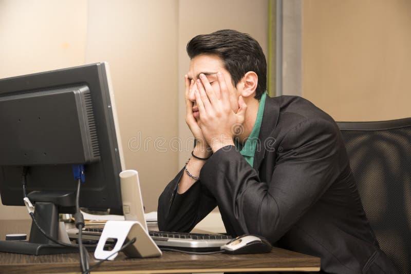 Müder gebohrter junger Geschäftsmann im Büro stockfotos