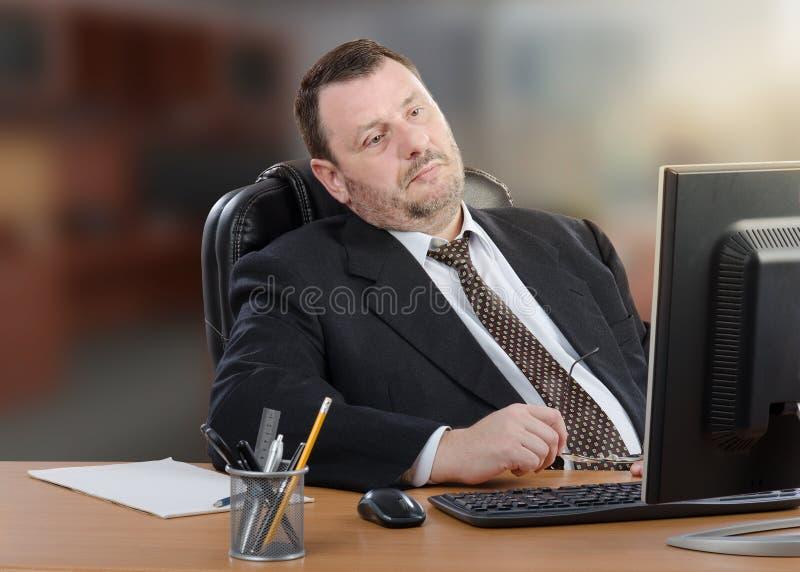 Müder Geschäftsmann betrachtet Computer stockbild