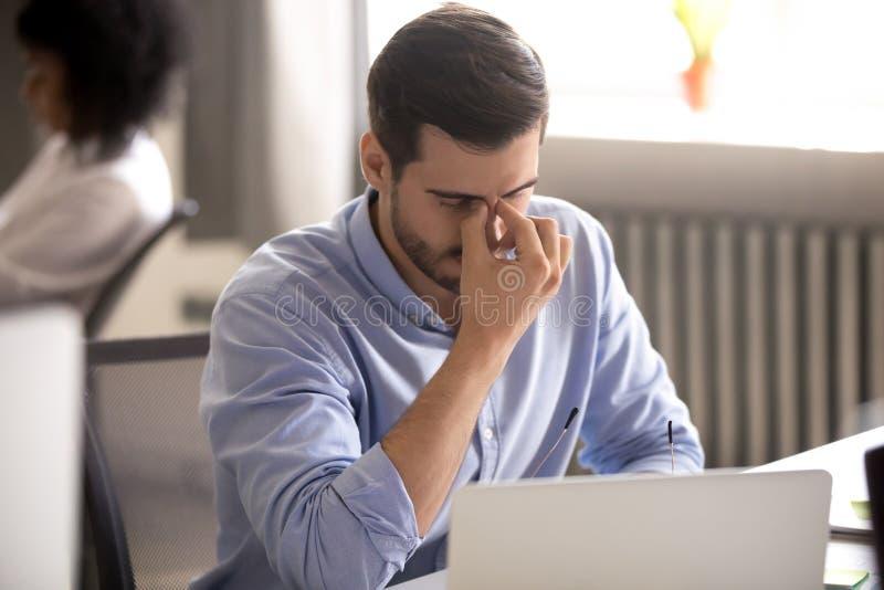 Müder Geschäftsmann, der Gläser nach Überstundencomputerarbeit entfernt lizenzfreies stockbild