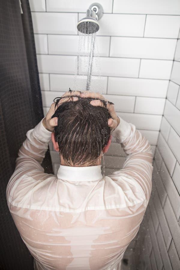 Müder Geschäftsmann im weißen Hemd, das seine Hände hinter seinem Kopf, unter der Dusche stehend unter dem Nachlaufen des warmen  stockbild