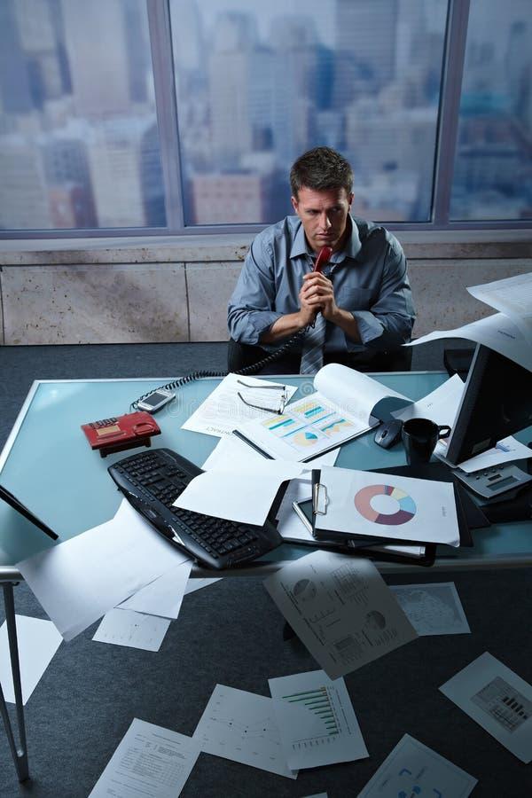 Müder Geschäftsmann mit Papieren ganz herum lizenzfreie stockbilder