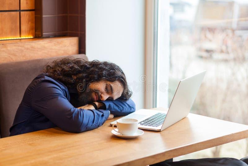 Müder hübscher junger erwachsener Mannfreiberufler in der zufälligen Art, die im Café mit dem Laptop, auf dem Tisch schlafend nac stockbild