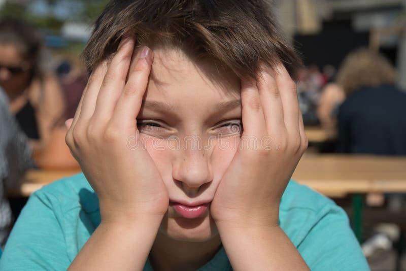 Müder Junge, der mit den Händen auf seinem Gesicht sitzt stockbilder