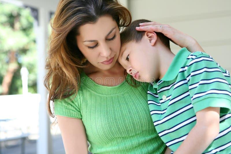 Müder Junge zu Hause mit Mutter lizenzfreie stockfotos