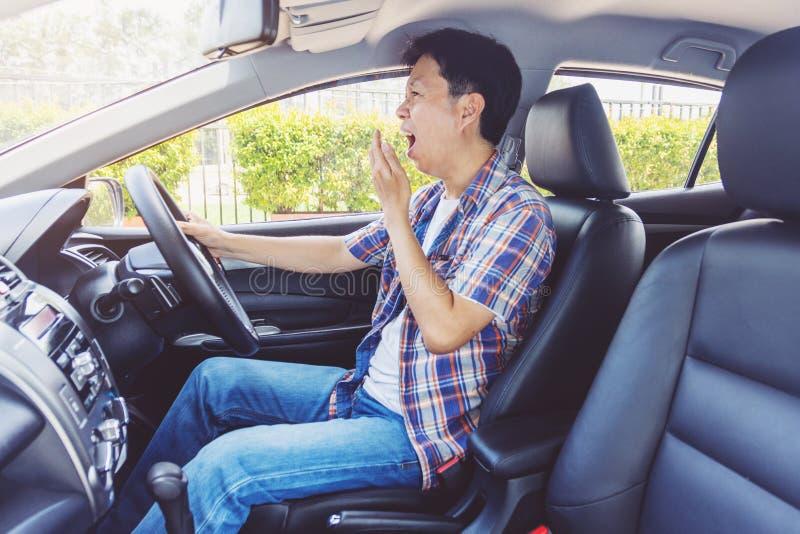 Müder junger Asien-Mann, der sein Auto fährt lizenzfreies stockfoto