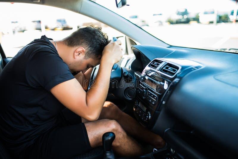 Müder junger gut aussehender Mann des Nahaufnahmeporträts mit der kurzen Aufmerksamkeitsspanne, sein Auto nach Überstunden fahren lizenzfreie stockbilder