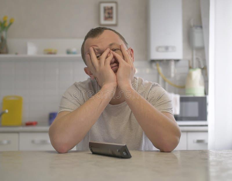 Müder junger Kerl, der auf dem Hintergrund der Küche sitzt stockfoto