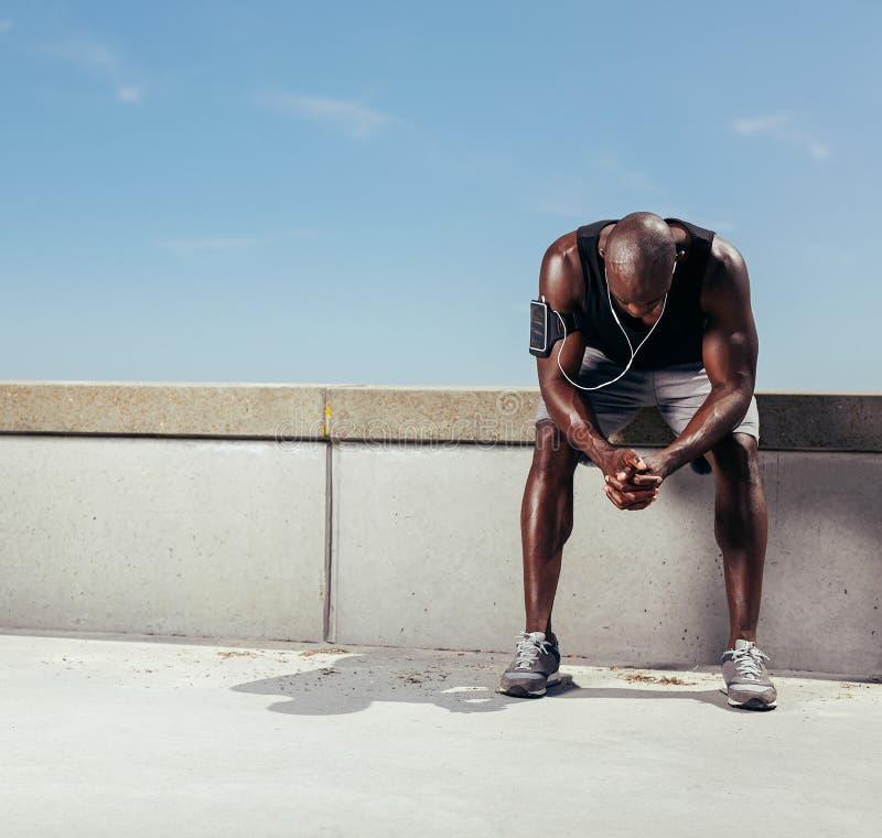 Müder junger Läufer, der sich vorbei lehnt, um seinen Atem zu fangen stockfotografie