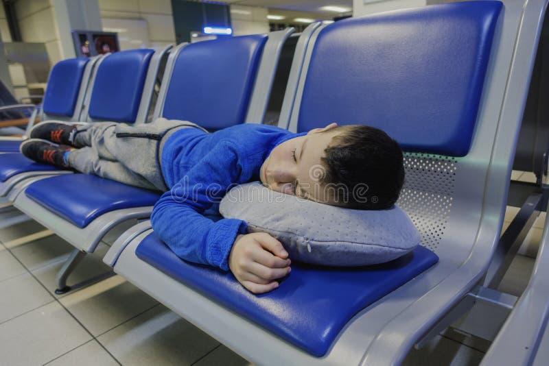 Müder kleiner Junge, der auf Stuhl bei der Aufwartung des Fluges am Flughafen schläft stockbild