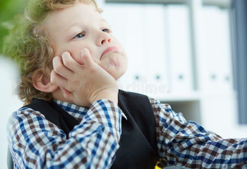 Müder kleiner Junge stützte seinen Kopf in seinen Händen und in Blicken am Monitor im Büro lizenzfreies stockbild