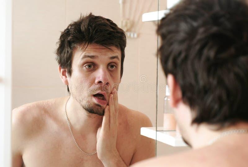 Müder Mann, der gerade Blicke an seiner Reflexion im Spiegel aufgewacht hat, schlägt seine Backe mit seiner Hand lizenzfreies stockfoto