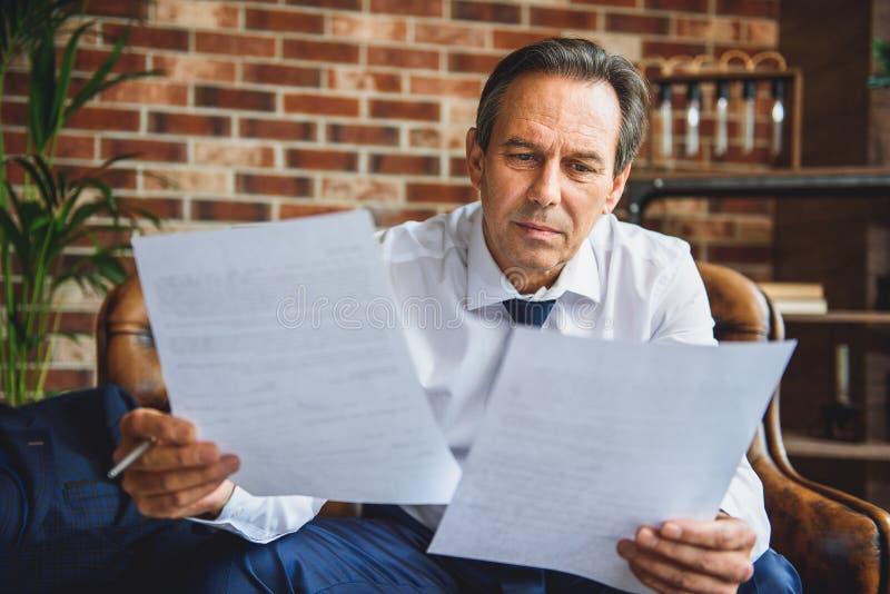 Müder Mann, der Papiere mit Aufmerksamkeit betrachtet stockbilder