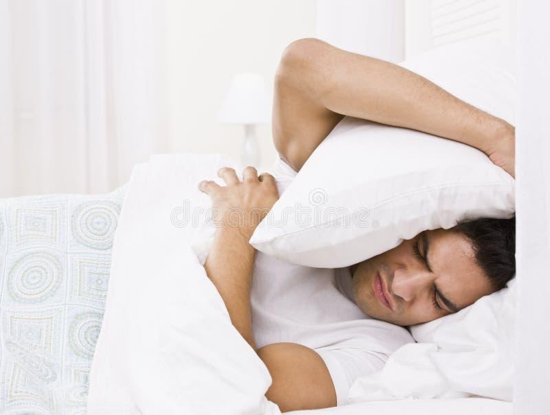 Müder Mann, der seinen Kopf mit Kissen versteckt stockbild
