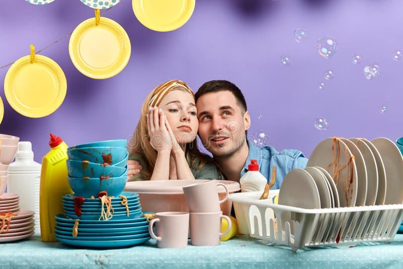 Müder Mann und die Frau, die einen Rest hat, beim Säubern kicthen Raum stockfoto