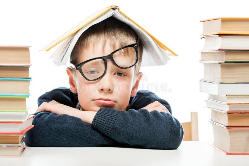 Müder Schüler und Stapel von Büchern auf weißem Hintergrund, Nahaufnahme lizenzfreie stockfotos