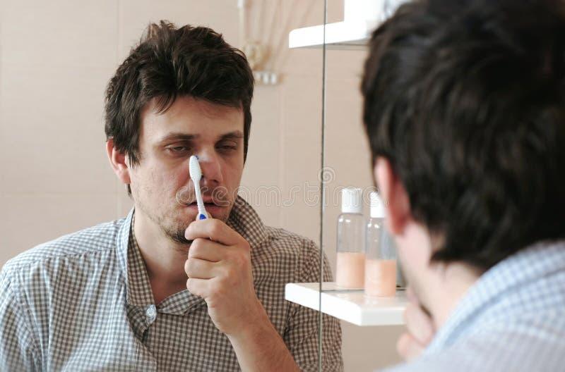 Müder schläfriger Mann mit einem Kater, der gerade Bürste seine Zähne aufgewacht hat, betrachtet seine Reflexion im Spiegel stockbild