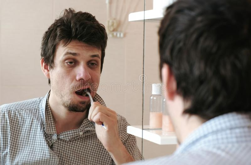 Müder schläfriger Mann mit einem Kater, der gerade Bürste seine Zähne aufgewacht hat, betrachtet seine Reflexion im Spiegel lizenzfreie stockbilder
