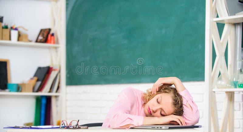 Müder Tutor schlafen am Arbeitsplatz ein Müdes Studentenmageres auf Schreibtisch Erschöpfende Lektion Frau müde im Schulklassenzi stockfotografie